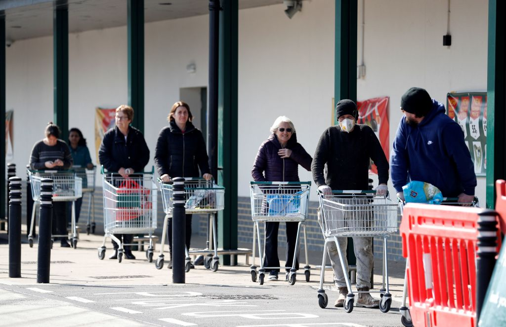 Shoppers observe social distancing as they wait in a queue outside a supermarket in Fleet, Hampshire. (Photo by ADRIAN DENNIS/AFP via Getty Images)