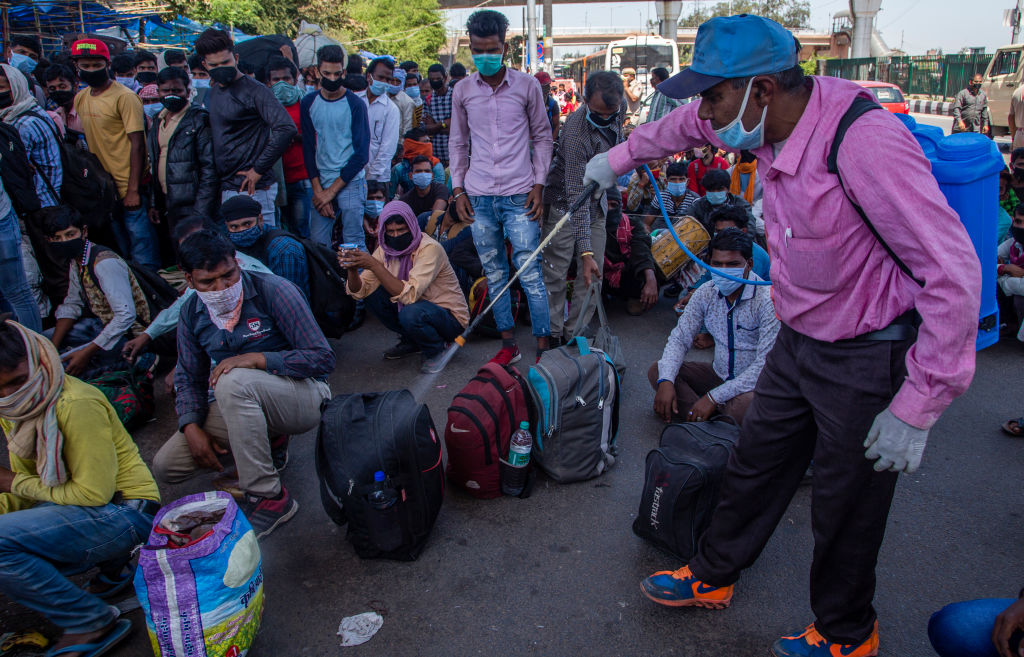 An Indian health worker sprays disinfectant on the luggage of migrant workers and labourers along with their families stuck in the national capital, as they wait to board buses to return to their native villages, as nationwide lockdown continues over the highly contagious coronavirus (COVID-19) in Ghaziabad, on the outskirts New Delhi, India. (Photo by Yawar Nazir/Getty Images)