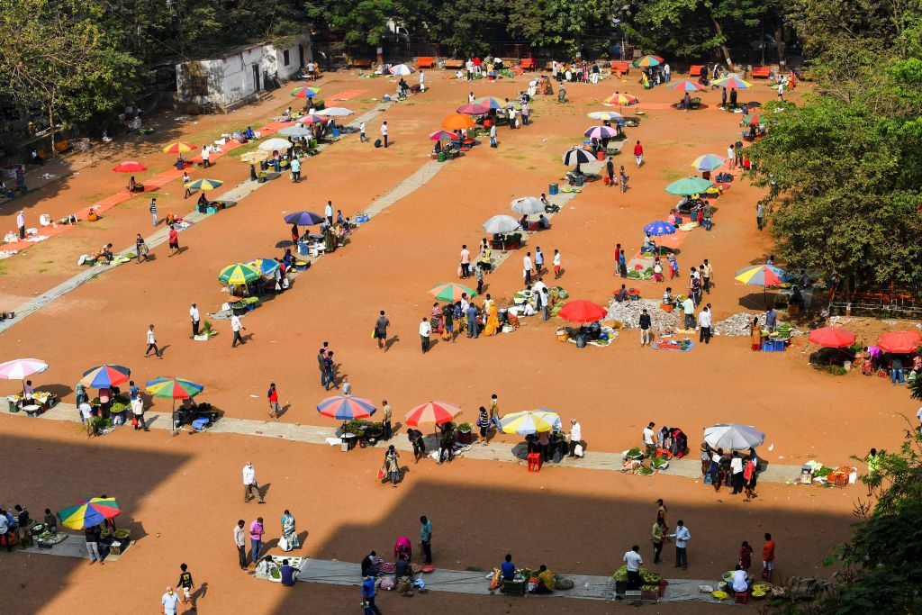 Vegetable vendors set up their stalls maintaining social distance at an open field during a government-imposed nationwide lockdown as a preventive measure against the spread of the COVID-19 coronavirus in Mumbai on March 30, 2020. (Photo by INDRANIL MUKHERJEE/AFP via Getty Images)