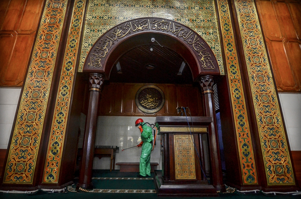 A medical staff sprays disinfectant at a mosque in West Java, Indonesia on March 18. (Photo: Antara Foto/Adeng Bustomi/ via Reuters)