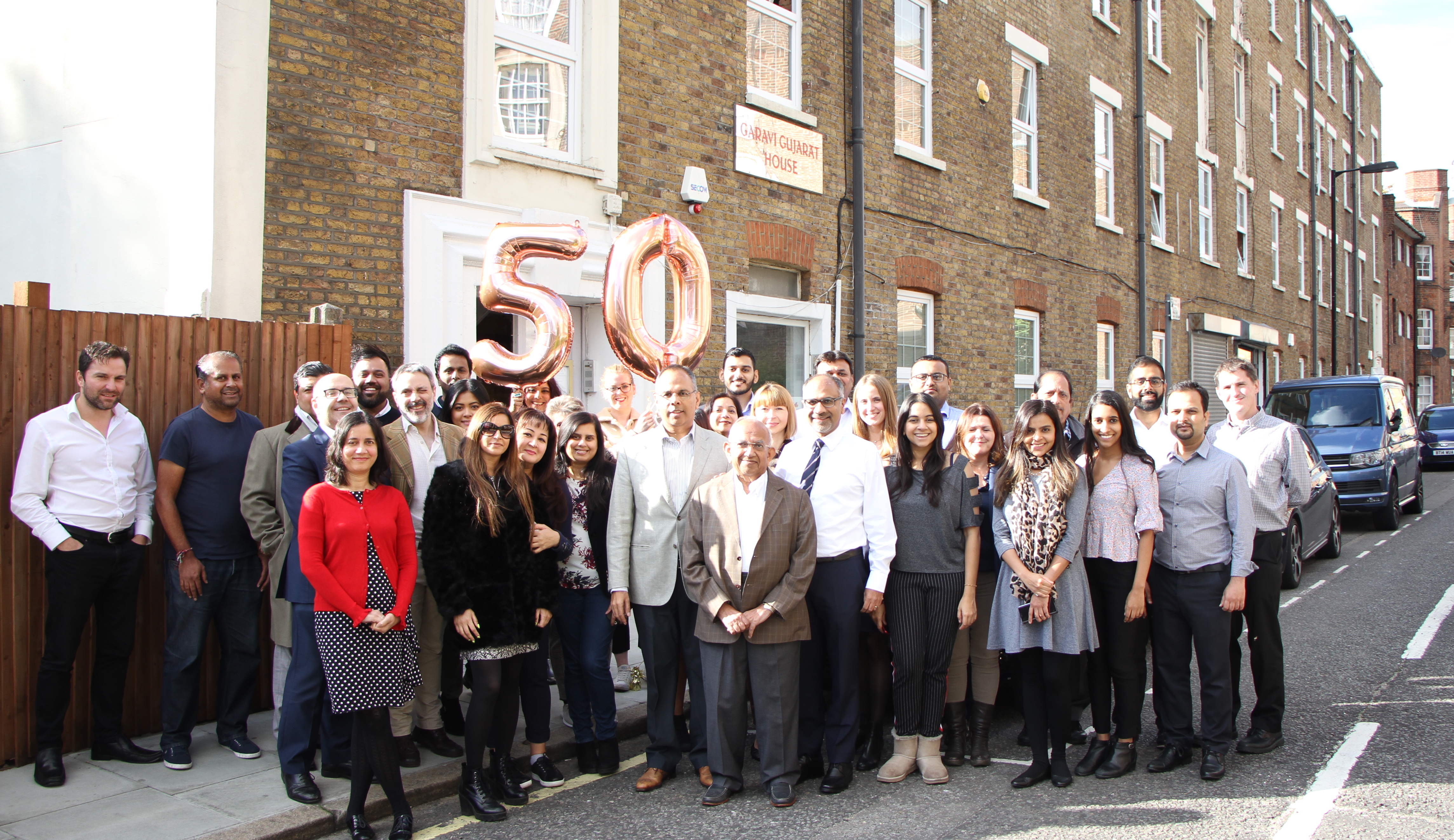 IMPARTING WISDOM: AMG staff with  Ramniklal Solanki (centre, in brown jacket)  and members of the Solanki family in front  of the company's London offices to mark  50 years since the launch of Garavi Gujarat