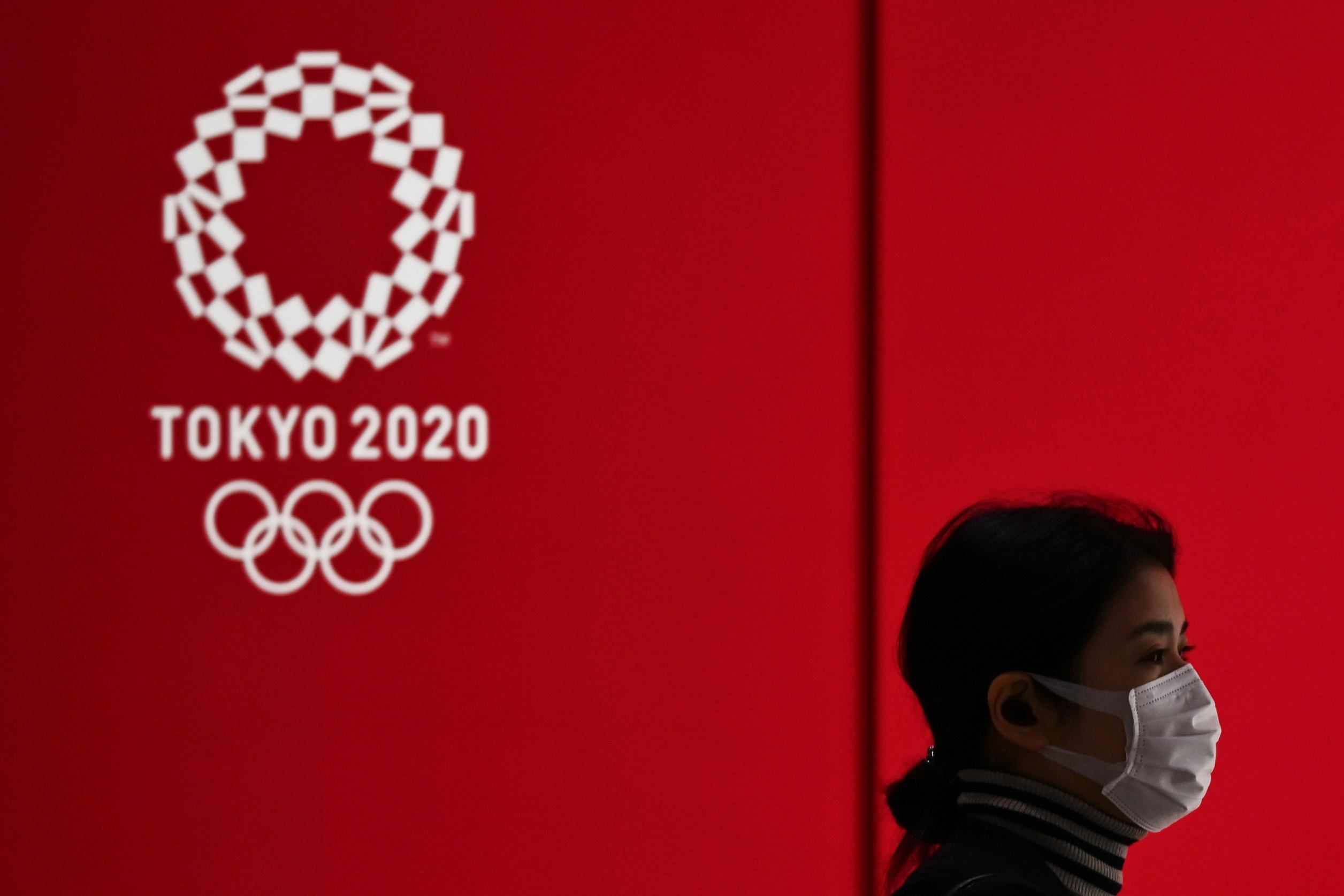 TOPSHOT - A woman in a face mask walks past a display showing the Tokyo 2020 Olympic Games logo in Tokyo on March 24, 2020. (Photo by CHARLY TRIBALLEAU / AFP) (Photo by CHARLY TRIBALLEAU/AFP via Getty Images)