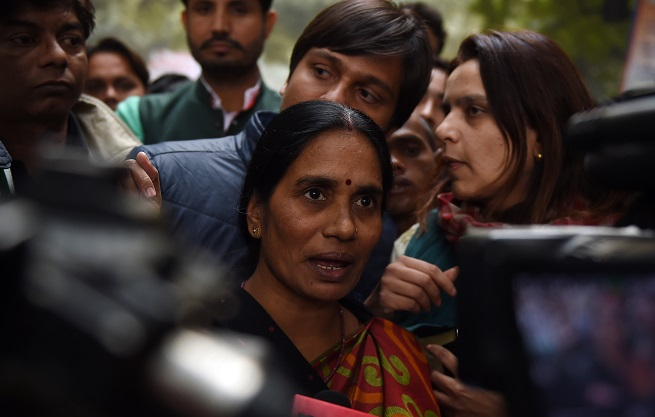 The mother of Indian gangrape victim 'Nirbhaya' (C) talks to the media (Photo: MONEY SHARMA/AFP via Getty Images).