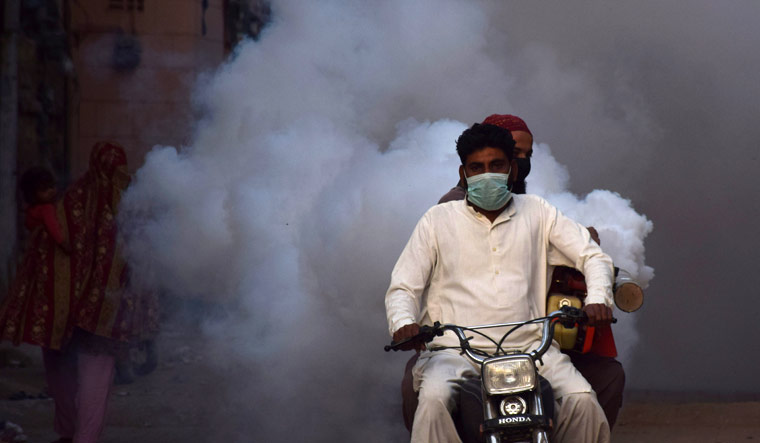 Health workers on motor-bike fumigate, as a preventive measure against coronavirus, along a street in Hyderabad, Pakistan March 15, 2020 | Reuters/Yasir Ali