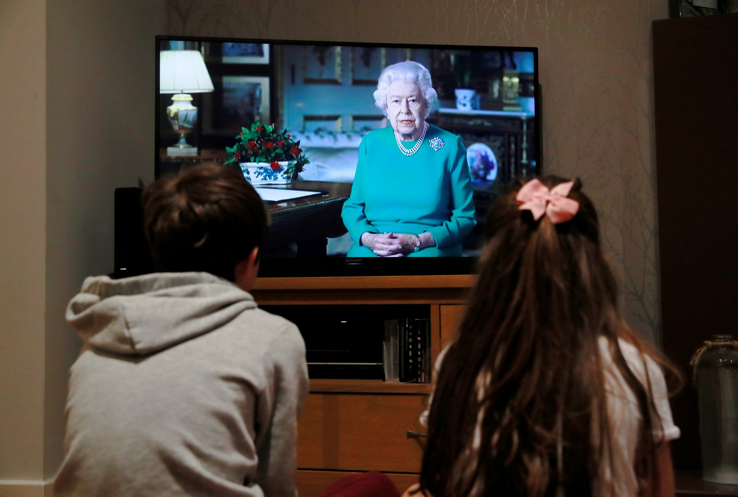 Noah (9) and Milly (7) watch Britain's Queen Elizabeth II during a televised address to the nation at their home, as the spread of the coronavirus disease (COVID-19) continues, Hertford, Britain, April 5, 2020. REUTERS/Andrew Couldridge