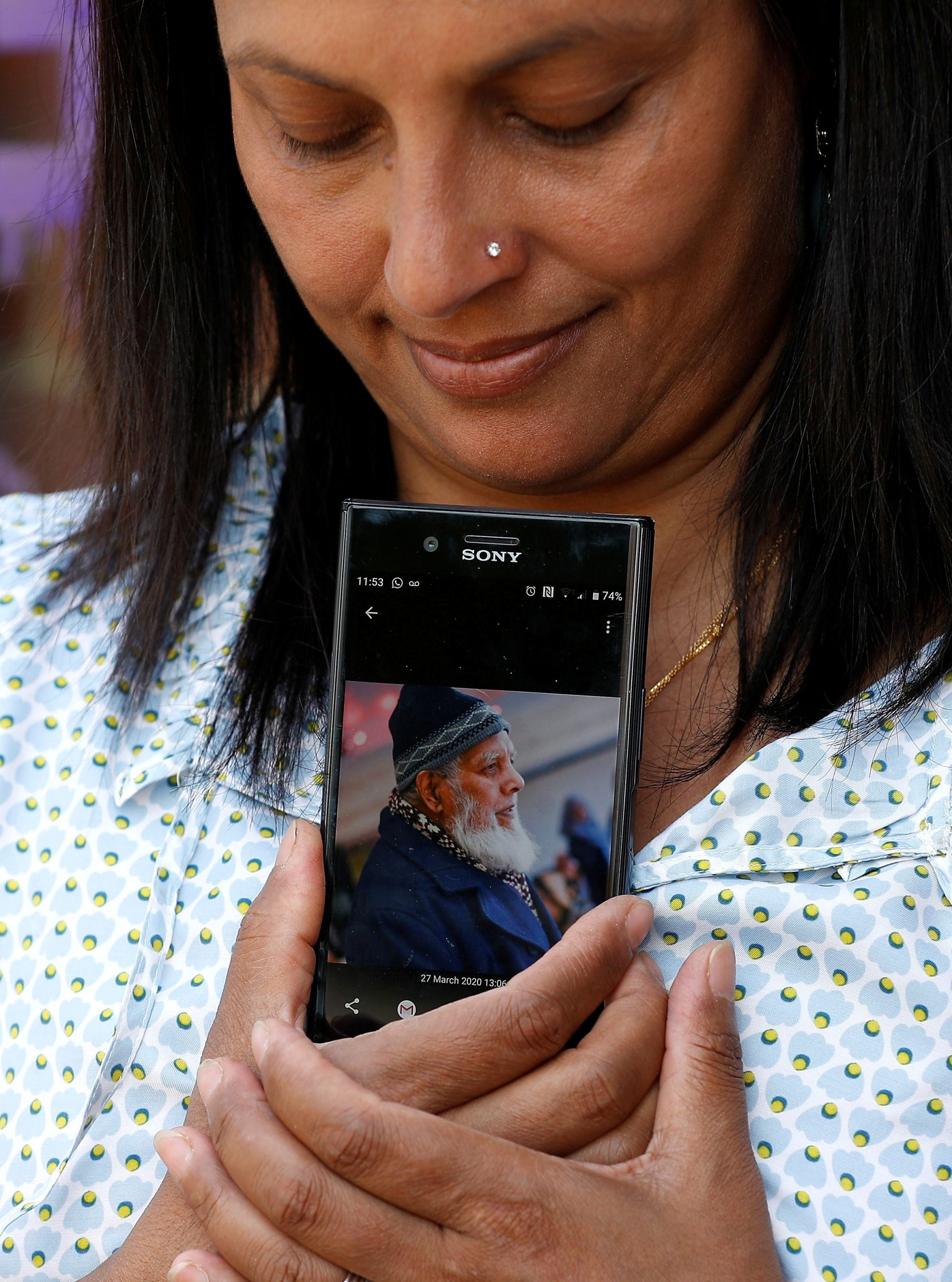 Luthfa Hood whose father, Jamshad Ali, recently passed away shows his picture at her home, as the spread of the coronavirus disease (COVID-19) continues, in Dorking, Britain April 9, 2020. (REUTERS/Peter Nicholls)