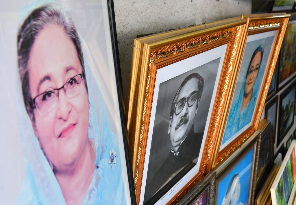 FILE PHOTO: Photographs of Bangladesh's founding father Sheikh Mujibur Rahman (C) and his daughter Prime Minister Sheikh Hasina (L) are displayed at a photo framing shop in Dhaka. (INDRANIL MUKHERJEE/AFP via Getty Images)