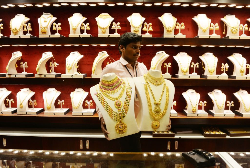 """FILE PHOTO: An Indian sales assistant arranges gold ornaments during the Hindu festival of """"Akshaya Tritiya"""" at a jewellery shop in Chennai. (ARUN SANKAR/AFP via Getty Images)"""