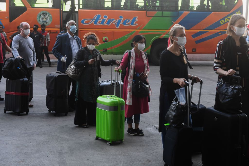 Foreign nationals wearing face masks line up outside the departure terminal of the Netaji Subhash Chandra Bose International Airport to board a special evacuation flight during a government-imposed nationwide lockdown as a preventive measure against the COVID-19 coronavirus, in Kolkata. (Photo: DIBYANGSHU SARKAR/AFP via Getty Images)