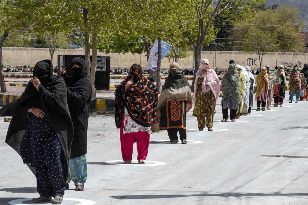 People stand in circles marked on the ground to maintain social distanciation as they wait to collect free dry rations from the Saylani Welfare Trust during a government-imposed nationwide lockdown as a preventive measure against the COVID-19 coronavirus, in Quetta  (Photo by BANARAS KHAN/AFP via Getty Images)