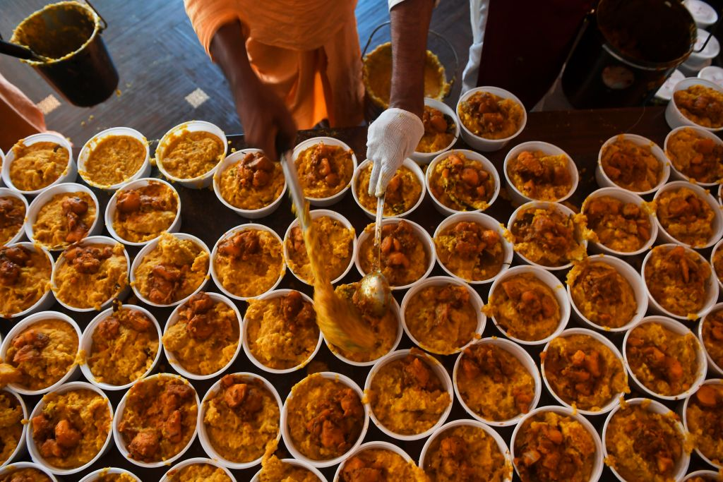 Members of the International Society for Krishna Consciousness (ISKCON) prepare food boxes before distributing them among migrant workers and people in need during a government-imposed nationwide lockdown as a preventive measure against the COVID-19 coronavirus, in Kolkata on April 1, 2020. (Photo by DIBYANGSHU SARKAR/AFP via Getty Images)