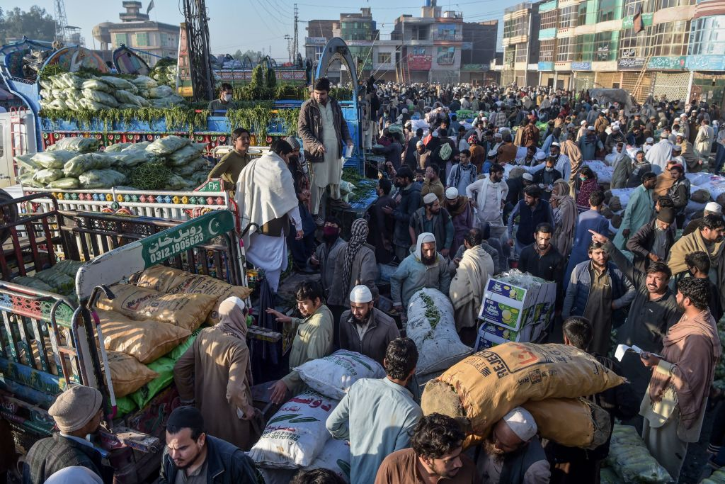 Traders and customers gather to bargain prices of commodities at a crowded vegetable market during a government-imposed nationwide lockdown as a preventive measure against the COVID-19 coronavirus, in Peshawar. (Photo by ABDUL MAJEED/AFP via Getty Images)