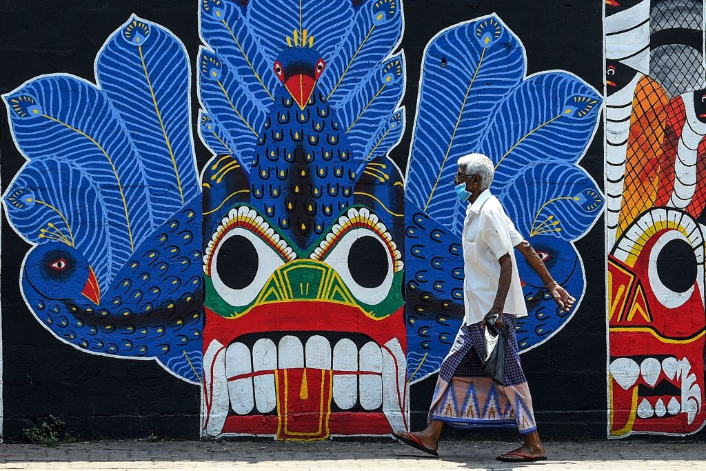 A man wearing a facemask walks past a mural during a government-imposed nationwide lockdown as a preventive measure against the COVID-19 coronavirus, in Colombo on April 3, 2020. (Photo by Ishara S. KODIKARA / AFP) (Photo by ISHARA S. KODIKARA/AFP via Getty Images)