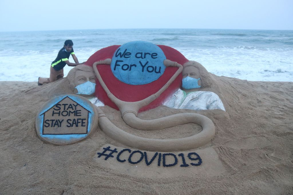 """Indian artist Sudarsan Pattnaik puts some final touches as he makes a sand sculpture depicting doctors wearing protective facemasks with a message reading """"We are For You"""", """"Stay Home Stay Safe"""" at Puri beach in Puri on April 3, 2020. (Photo by STR/AFP via Getty Images)"""