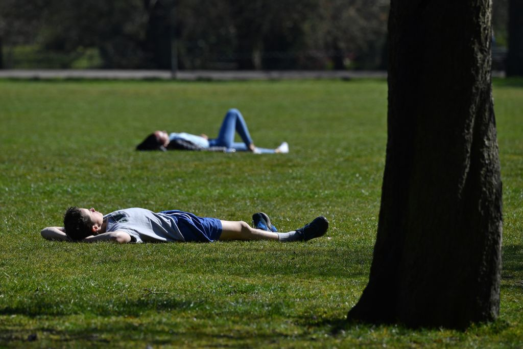 People sunbathe in Greenwich Park in central London on April 5, 2020. (Photo by Ben STANSALL / AFP) (Photo by BEN STANSALL/AFP via Getty Images)