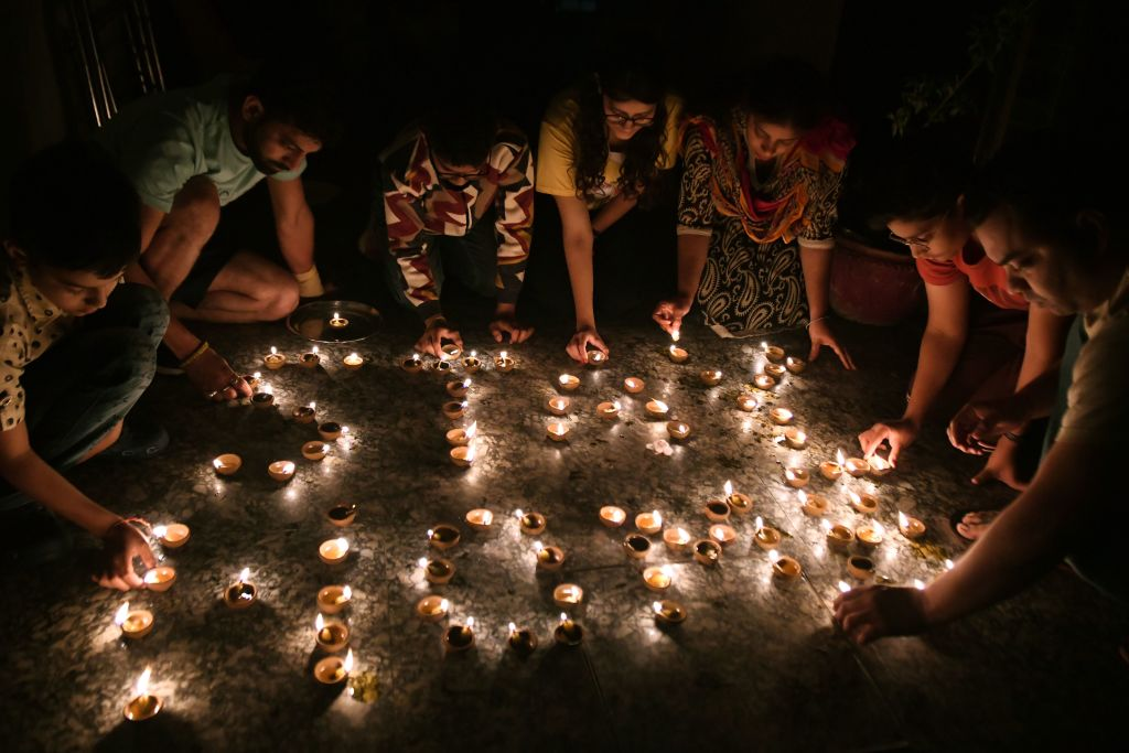 """A resident light diya or oil lamps forming the words """"Stay Home"""" outside their home to observe a nine-minute vigil called by India's Prime Minister in a show of unity and solidarity in the fight against the coronavirus pandemic in Amritsar on April 5, 2020. (Photo by NARINDER NANU / AFP) (Photo by NARINDER NANU/AFP via Getty Images)"""