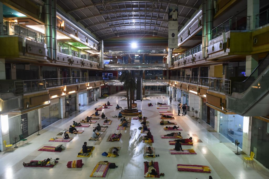 File photo of migrant workers resting at the closed JP Iscon Mall, which was used as a temporay shelter, during a government-imposed nationwide lockdown, in Ahmedabad. (Photo: by SAM PANTHAKY/AFP via Getty Images)