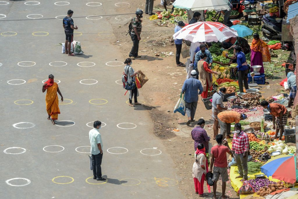 People walk in an area with circles marked on the floor for social distancing as they buy groceries at a temporary market set up at a bus stand during a government-imposed nationwide lockdown as a preventive measure against the COVID-19 coronavirus, in Chennai on April 7, 2020. (Photo by ARUN SANKAR/AFP via Getty Images)