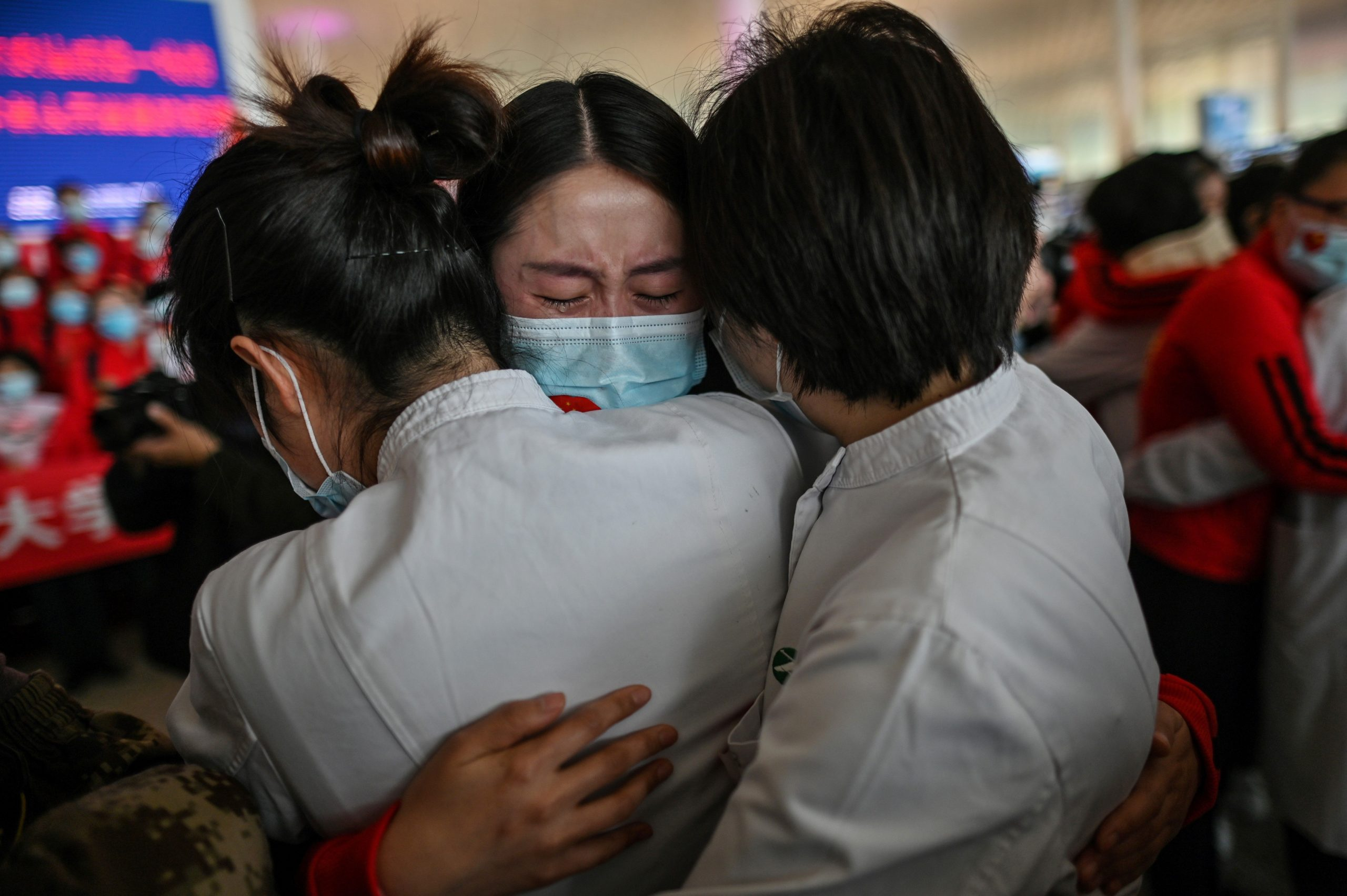 A medical staff member from Jilin Province (C) cries while hugging nurses from Wuhan after working together during the COVID-19 coronavirus outbreak in Wuhan during a ceremony at the Tianhe Airport after it was reopened today, in Wuhan in China's central Hubei province on April 8, 2020. - Thousands of Chinese travellers rushed to leave COVID-19 coronavirus-ravaged Wuhan on April 8 as authorities lifted a more than two-month prohibition on outbound travel from the city where the global pandemic first emerged. (Photo by Hector RETAMAL / AFP) (Photo by HECTOR RETAMAL/AFP via Getty Images)