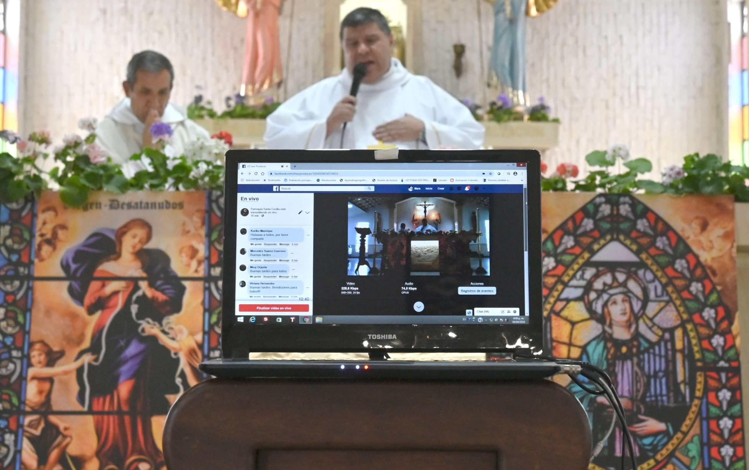Colombian priest Mauricio Cuellar (C) gives mass from the empty Santa Cecilia church in Bogota to online parishioners as a preventive measure against the spread of the novel coronavirus COVID-19, on April 9, 2020. - Colombia extended mandatory preventive isolation due to COVID-19 until at least April 27. (Photo by Raul ARBOLEDA / AFP)