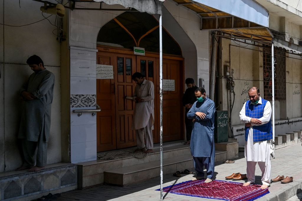 A few worshippers offer Friday prayers outside a closed mosque during a government-imposed nationwide lockdown as a preventive measure against the COVID-19 coronavirus, in Islamabad on April 10, 2020. (Photo by AAMIR QURESHI/AFP via Getty Images)