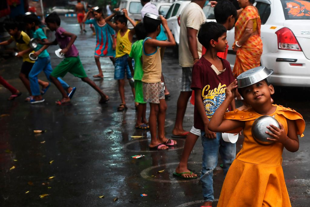Children stand in queue to collect food as its rain, during a government-imposed nationwide lockdown as a preventive measure against the COVID-19 coronavirus, in Kolkata on April 12, 2020. (Photo by DIBYANGSHU SARKAR/AFP via Getty Images)