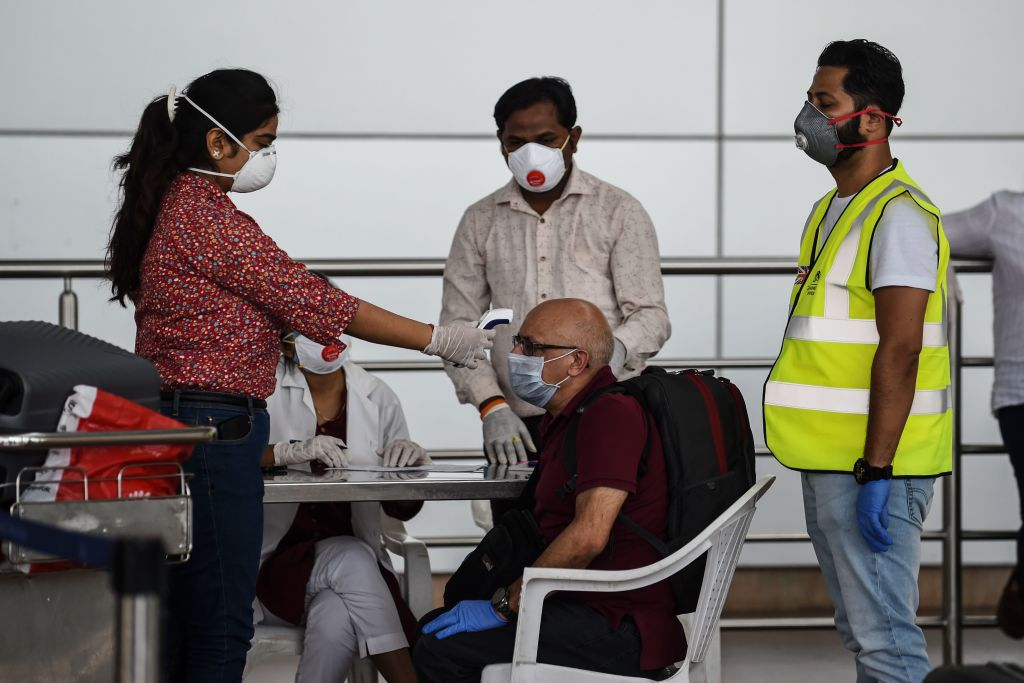 A doctor checks the body temperature of a British national before boarding a special British Airways flight at the Sardar Vallabhbhai Patel International Airport in Ahmedabad on April 13, 2020. (Photo: SAM PANTHAKY/AFP via Getty Images)
