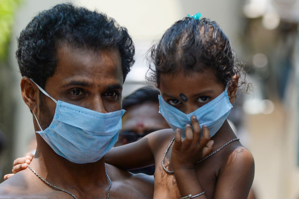 A migrant worker and his daughter wait to get food at a camp during a government-imposed nationwide lockdown as a preventive measure against the spread of the COVID-19 coronavirus in Chennai on April 16, 2020. (Photo by ARUN SANKAR/AFP via Getty Images)