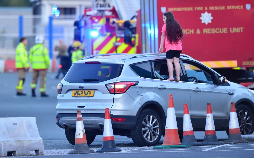 "A girl stands on the edge of a car window to get a better view ahead of a national ""clap for carers"" to show thanks for the work of frontline workers around the country as they battle the coronavirus pandemic, at Aintree University Hospital in Liverpool, on April 16, 2020. (Photo: ANTHONY DEVLIN/AFP via Getty Images)"