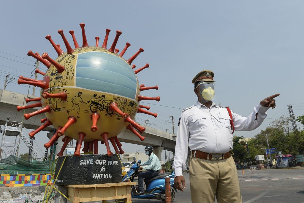A traffic officer stands beside a coronavirus-themed globe at a traffic junction as he checks commuters travelling during a government-imposed nationwide lockdown as a preventive measure against the COVID-19 coronavirus, in Hyderabad, on April 18, 2020. (Photo by NOAH SEELAM/AFP via Getty Images)