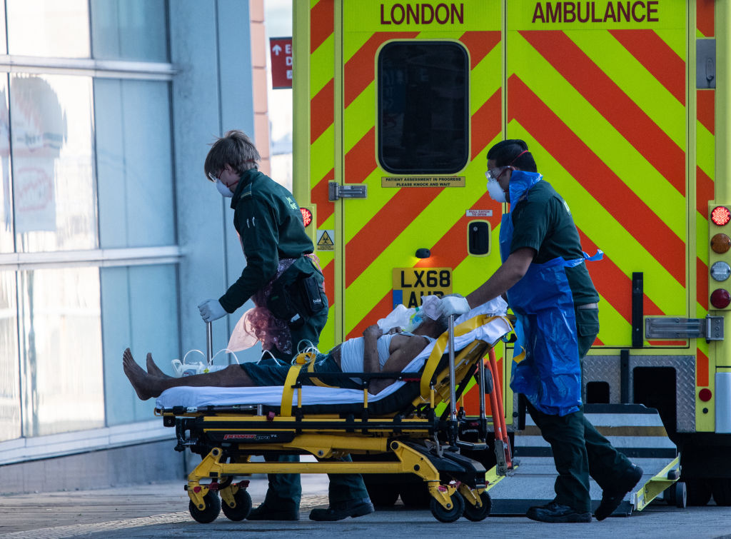 File photo: Ambulance paramedics wearing personal protective equipment help a patient from an ambulance into The Royal London Hospital. (Photo: Chris J Ratcliffe/Getty Images)