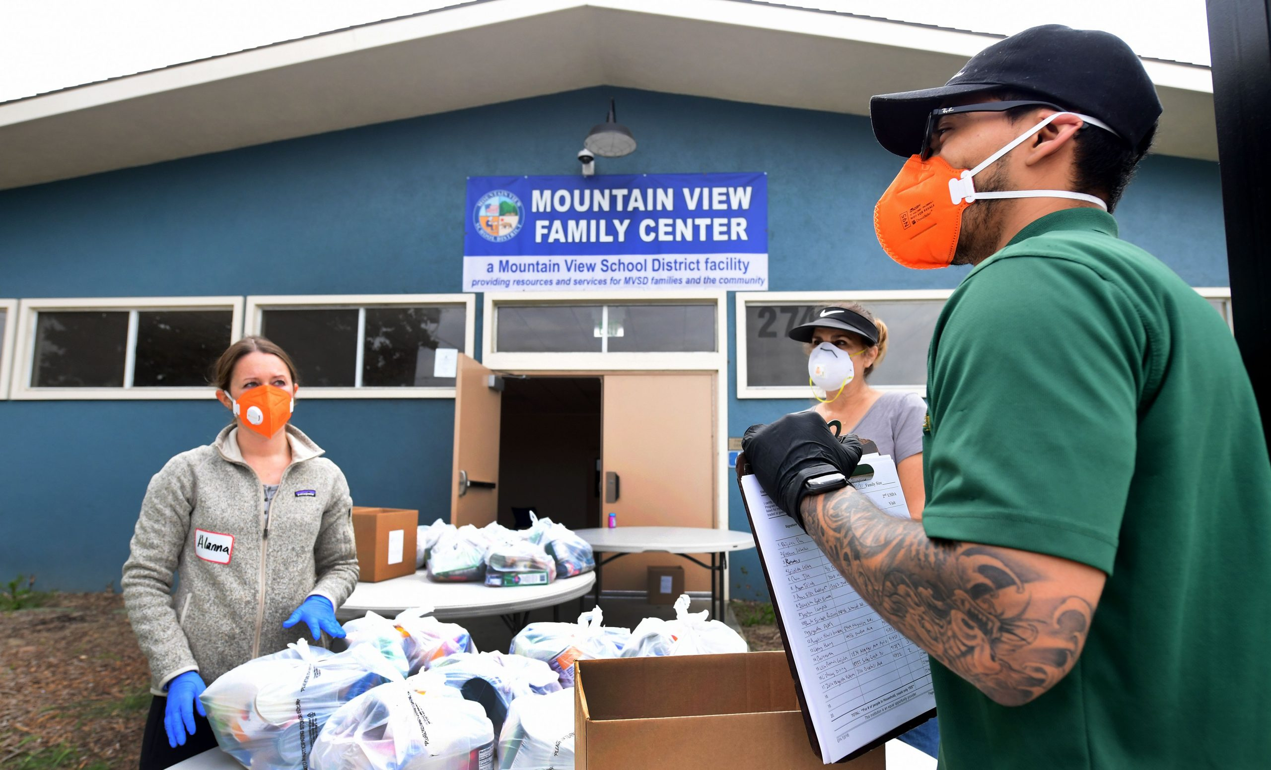 Volunteers in masks and gloves stand outside a food bank opened in response to the coronavirus pandemic on April 20, 2020 in El Monte, California. (Photo by Frederic J. BROWN / AFP)