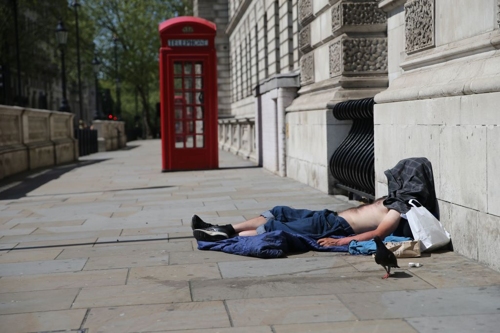 A homeless man rests on the pavement in Westminster, central London on April 22, 2020. (Photo: ISABEL INFANTES/AFP via Getty Images)