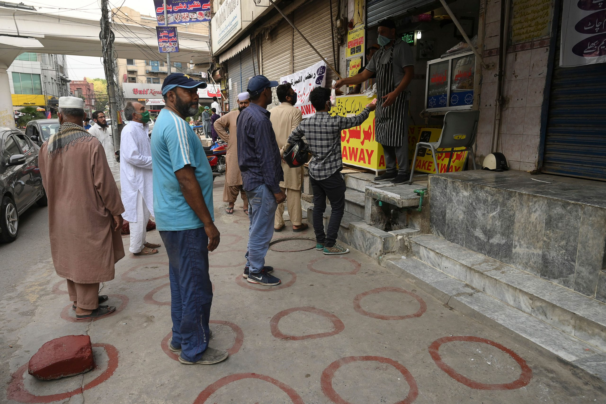 Muslim people maintaining social distance stand in line to buy food for Iftar on the first day of the Muslim holy month of Ramadan in Lahore on April 25, 2020. (Photo by ARIF ALI / AFP)