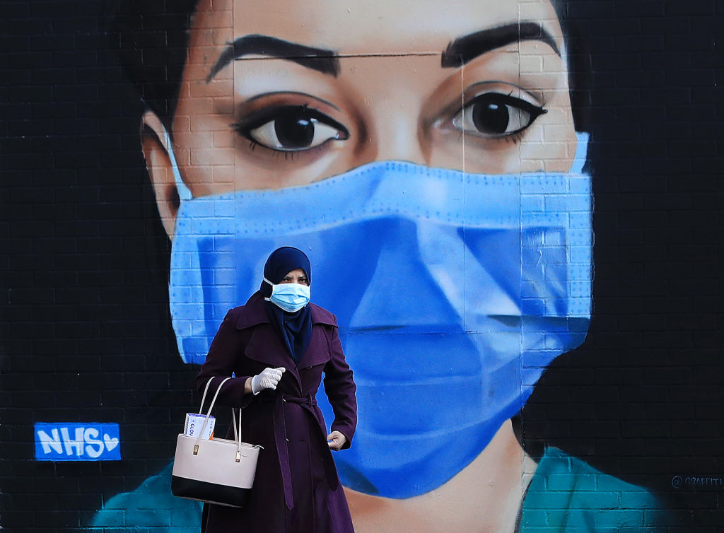 A woman wearing a face mask walks past a piece of street art depicting an NHS worker on April 21, 2020 in the Shoreditch area of London, England.  (Photo by Andrew Redington/Getty Images)