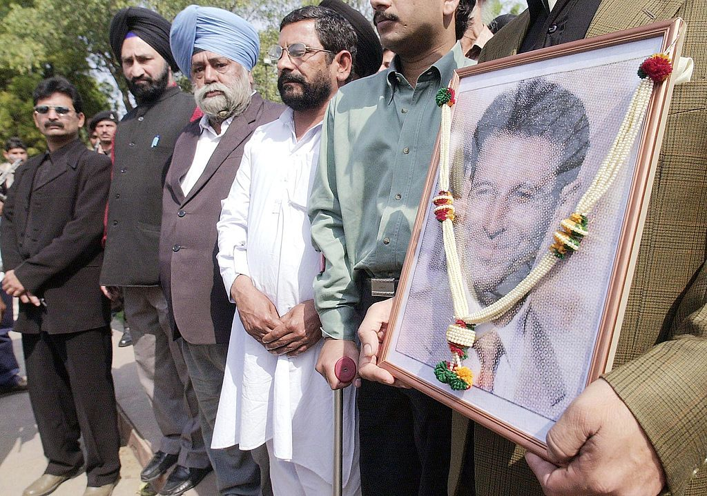 An activist of All India Anti-Terrorist Front hold a photograph of slain American journalist Daniel Pearl as they pay homage in New Delhi 24 February 2002.  PRAKASH SINGH/AFP via Getty Images)