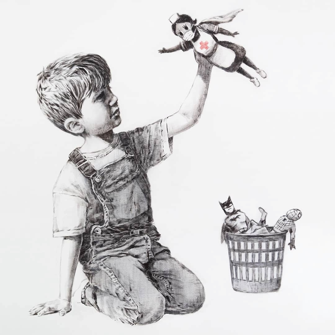 """A picture shows a drawing created by the street artist Banksy called """"Game Changer"""" as an appreciation for the NHS and is on display at Southampton General Hospital, in Southampton, Britain May 6, 2020 in this picture obtained from social media. It shows a boy dressed in dungarees playing with a nurse superhero toy with figures of Batman and Spiderman discarded in a basket on the floor. (@BANKSY INSTRAGRAM/via REUTERS)"""