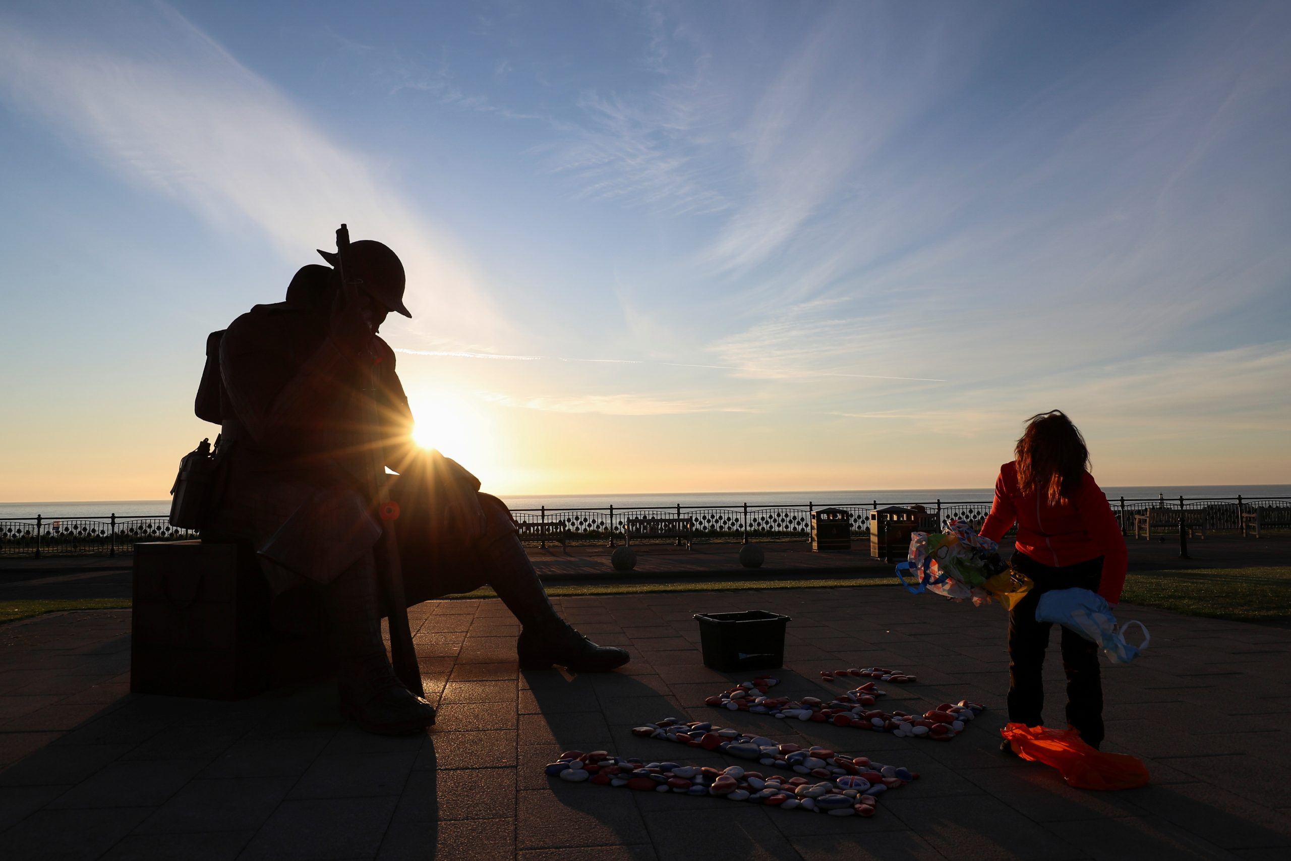 A woman is seen in front of the statue of soldier 'Tommy', a war statue by artist Ray Lonsdale, after making a sign with pebbles during sunrise on the 75th Anniversary of VE Day, in Seaham, on May 8, 2020. (REUTERS/Lee Smith)