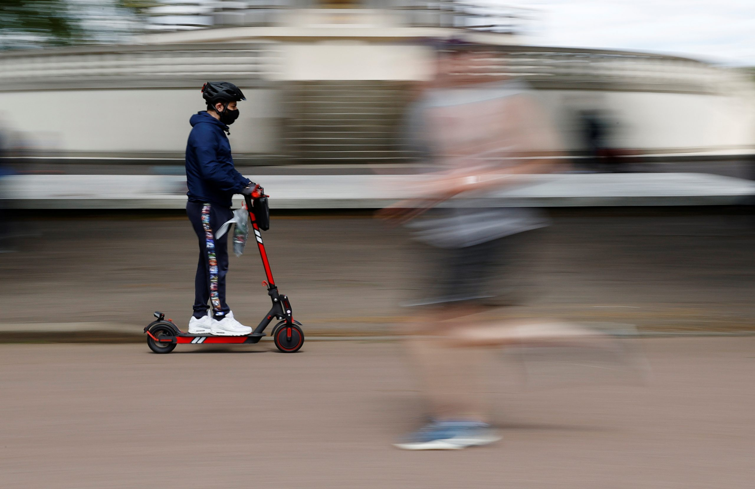 A man wearing a protective face mask on a scooter at Battersea Park in London on May 12, 2020. (REUTERS/John Sibley)