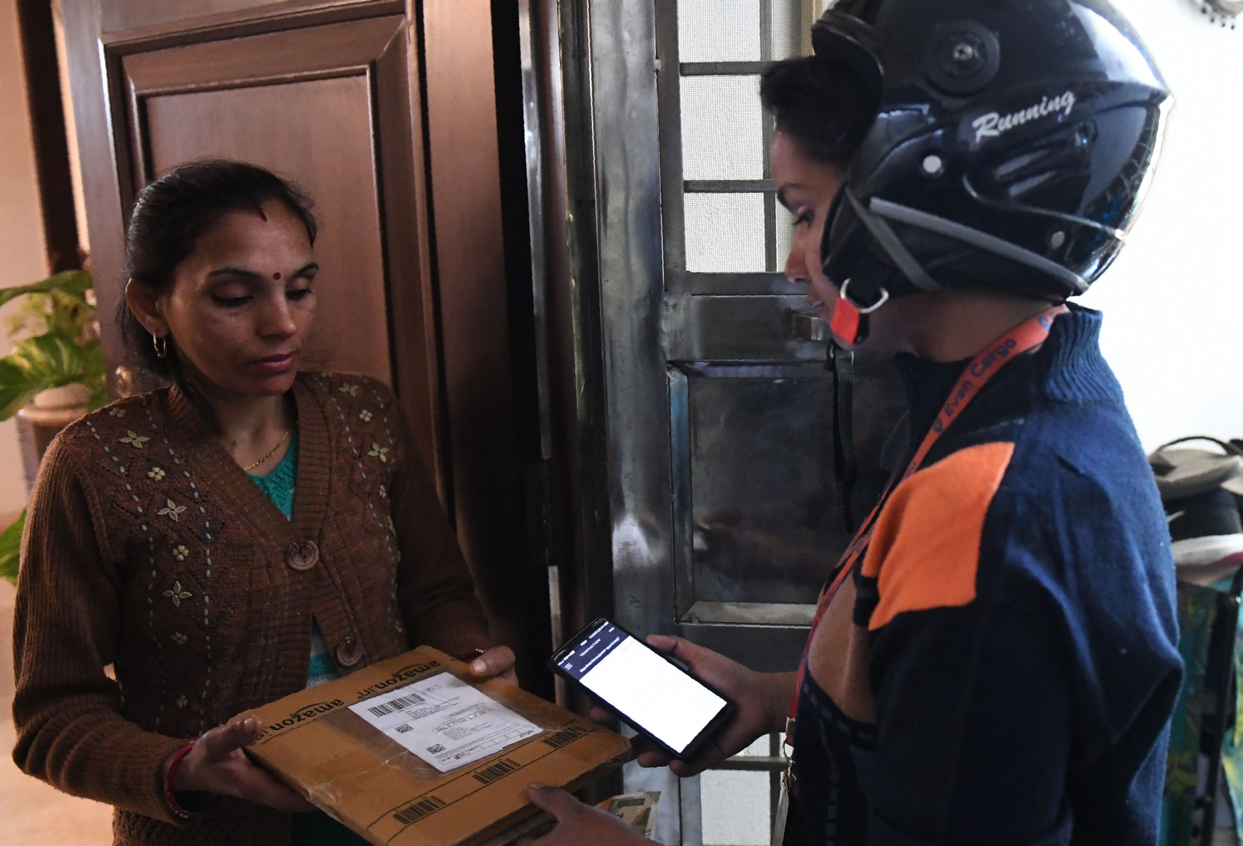 Indian delivery driver Jaya, 23, who works for Indias first women-only e-commerce logistics company, delivers a package in New Delhi on March 7, 2019. - Formed in 2016, Even Cargo trains and employs women from economically disadvantaged communities in professions that are traditionally inaccessible to them. These women are employed with Even Cargo for e-commerce logistics companies such as Amazon and Flipcart. (Photo by Money SHARMA / AFP)        (Photo credit should read MONEY SHARMA/AFP via Getty Images)