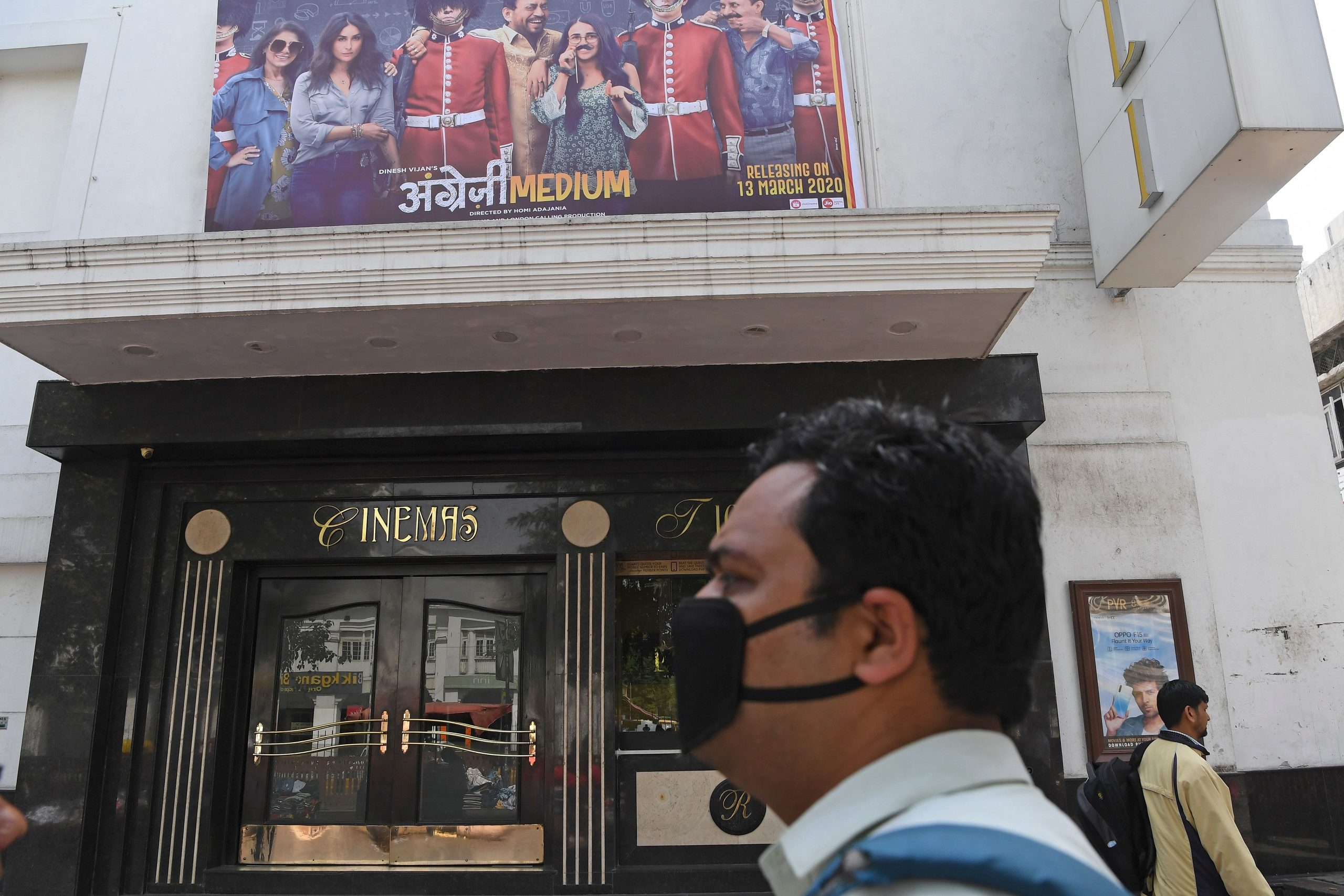A man wearing a facemask amid concerns of the spread of the COVID-19 coronavirus, walks pasts the closed Rivoli cinema complex in New Delhi on March 13, 2020. - India on March 12 reported its first coronavirus death as authorities ordered schools, theatres and cinemas closed in New Delhi for the rest of the month in a bid to keep the pandemic at bay. (Photo by Prakash SINGH / AFP) (Photo by PRAKASH SINGH/AFP via Getty Images)
