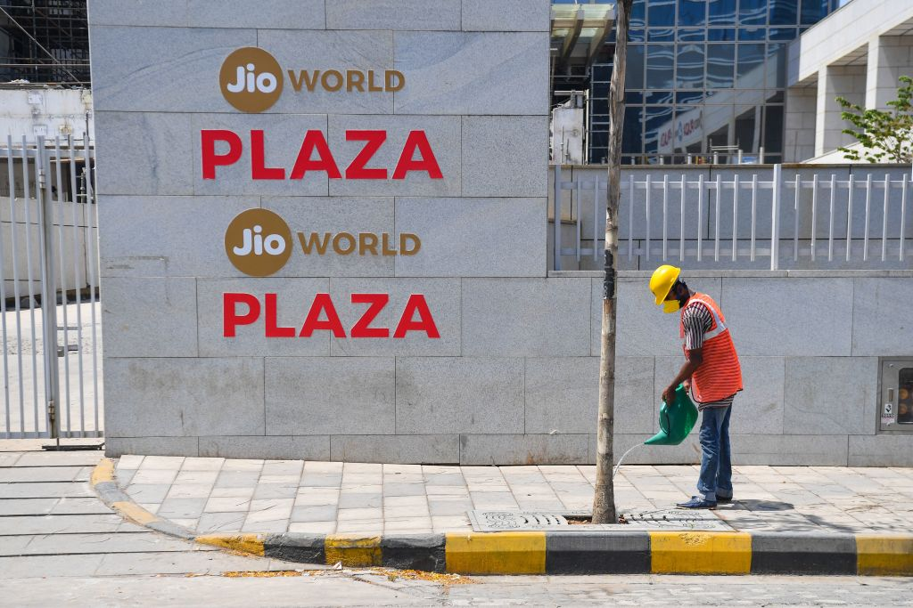 FILE PHOTO: A man waters a tree outside the Jio World Centre in Navi Mumbai (Photo by INDRANIL MUKHERJEE/AFP via Getty Images)