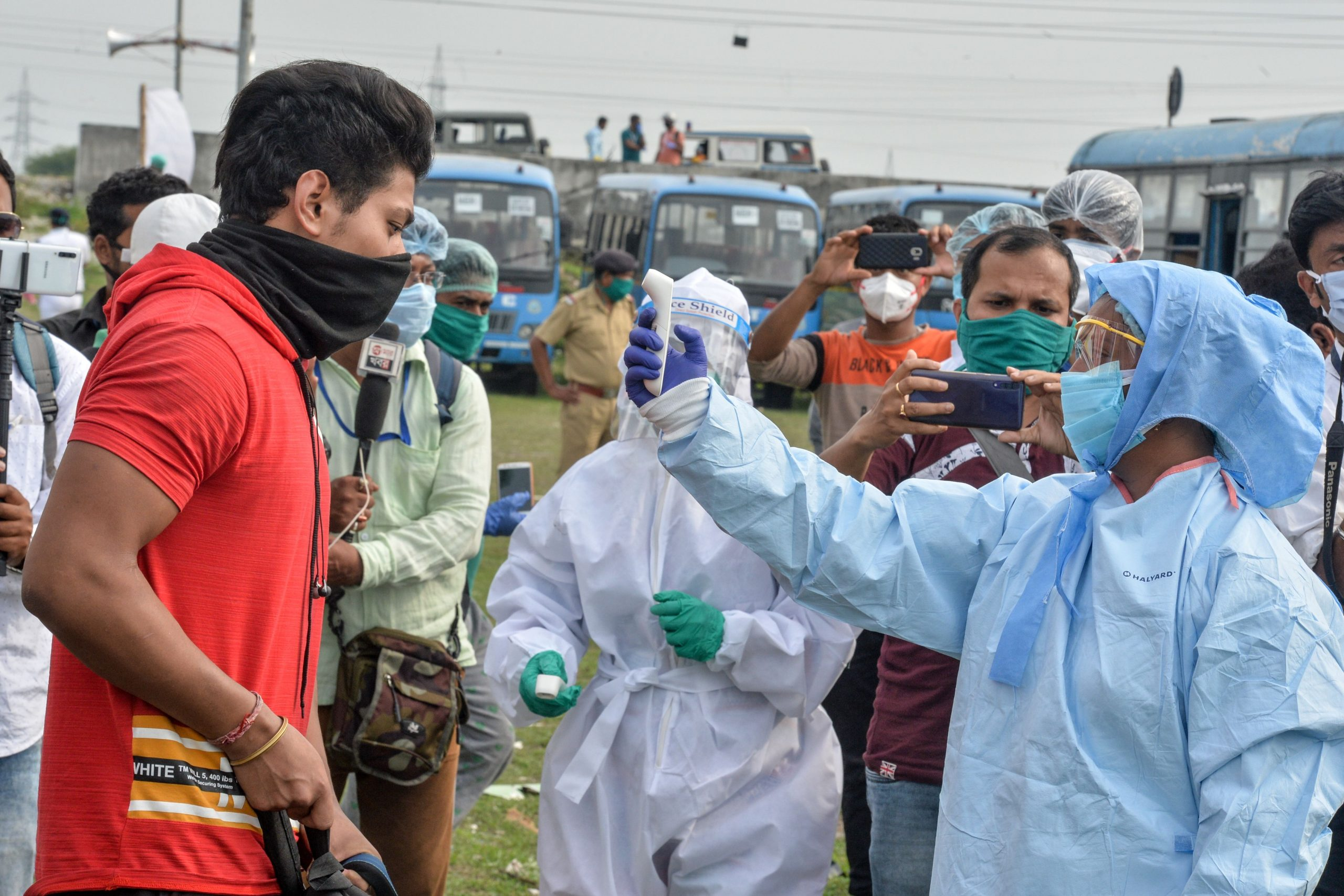 A health worker (R) checks the body temperature of a student after he arrived with others by bus from other states to their home in West Bengal state during a government-imposed nationwide lockdown as a preventive measure against the COVID-19 coronavirus, in Siliguri on May 1, 2020. (Photo by DIPTENDU DUTTA / AFP)