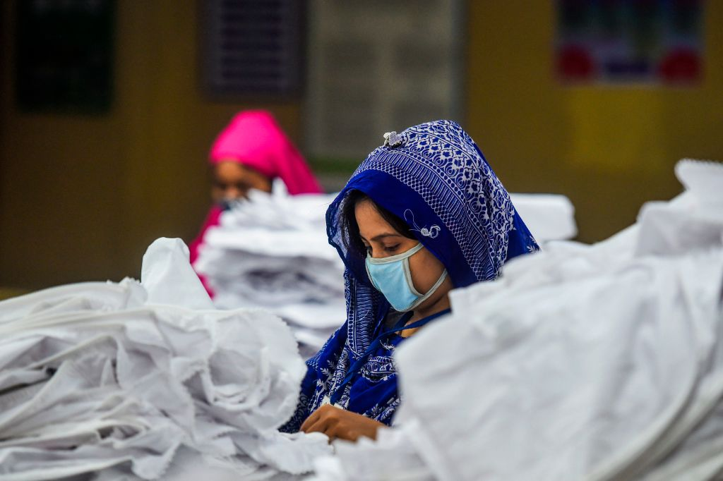 Labourers wearing facemasks work in a garment factory during a government-imposed lockdown as a preventive measure against the spread of the COVID-19 coronavirus in Dhaka. (Photo by MUNIR UZ ZAMAN/AFP via Getty Images)