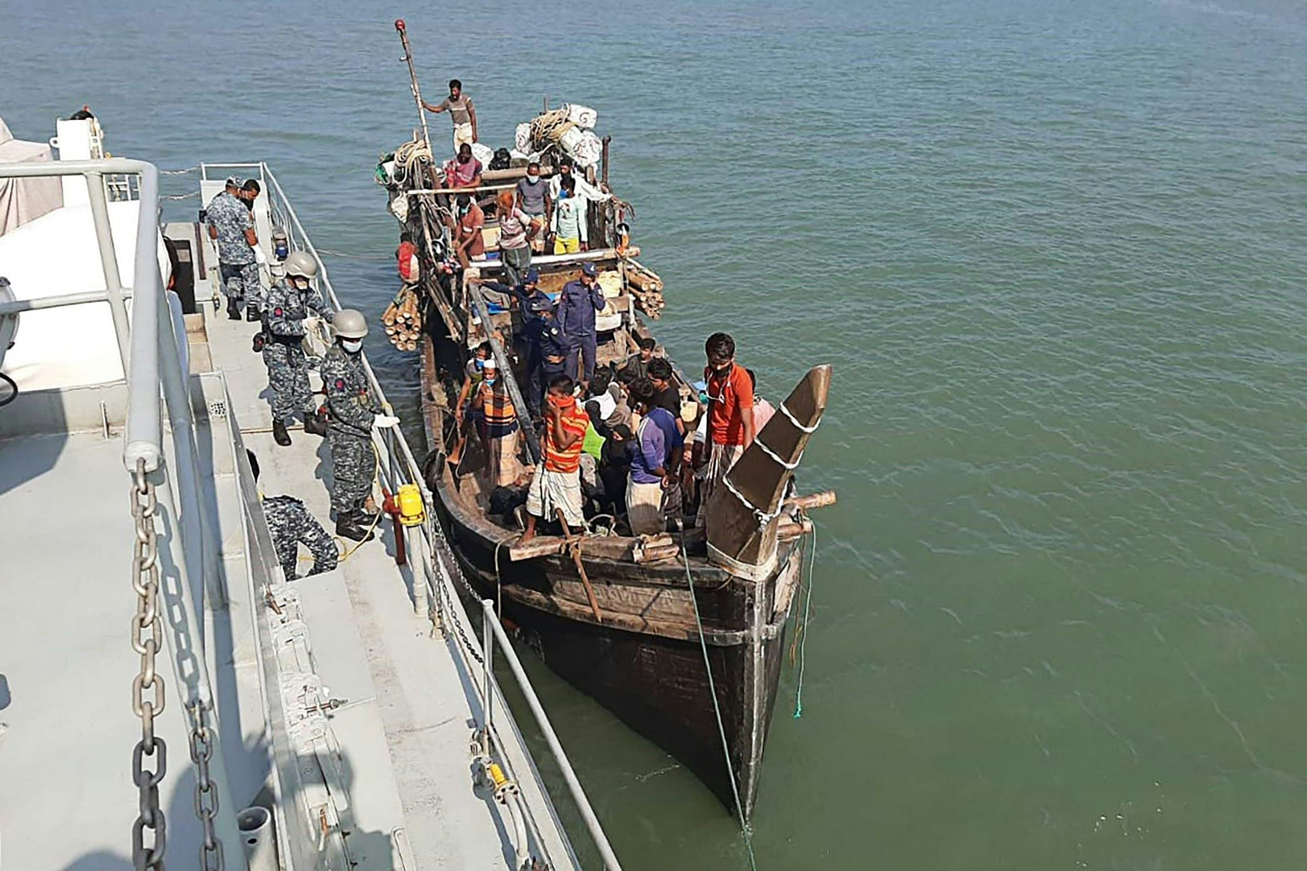 In this picture taken on May 2, 2020, Rohingya refugees stranded at sea are seen on a boat near the coast of Cox's Bazar. - Dozens of Rohingya refugees believed to have come from two boats stranded at sea for weeks as they tried to reach Malaysia landed on the Bangladesh coast on May 2, Rohingya community leaders said. (Photo by STR / AFP)