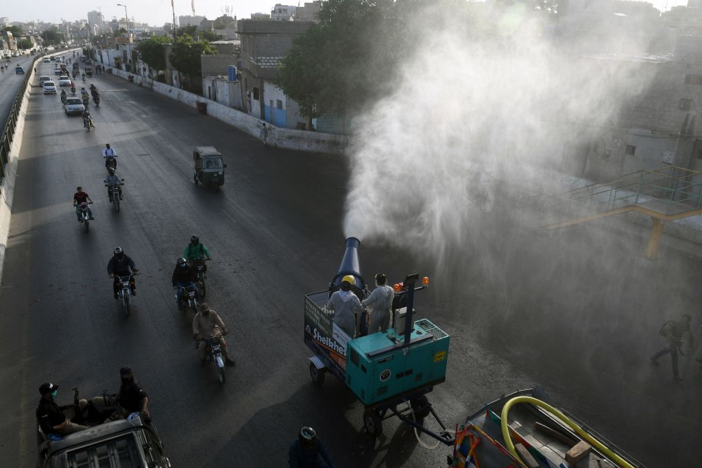 Workers sprays disinfectant along a road during a government-imposed nationwide lockdown as a preventive measure against the spread of the COVID-19 coronavirus, in Karachi on May 4, 2020. (Photo by ASIF HASSAN/AFP via Getty Images)