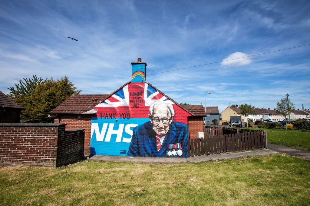 A street art graffiti mural, showing the  NHS logo, and an image of 100-year-old veteran Captain Tom Moore, in east Belfast. (Photo: PAUL FAITH/AFP via Getty Images)