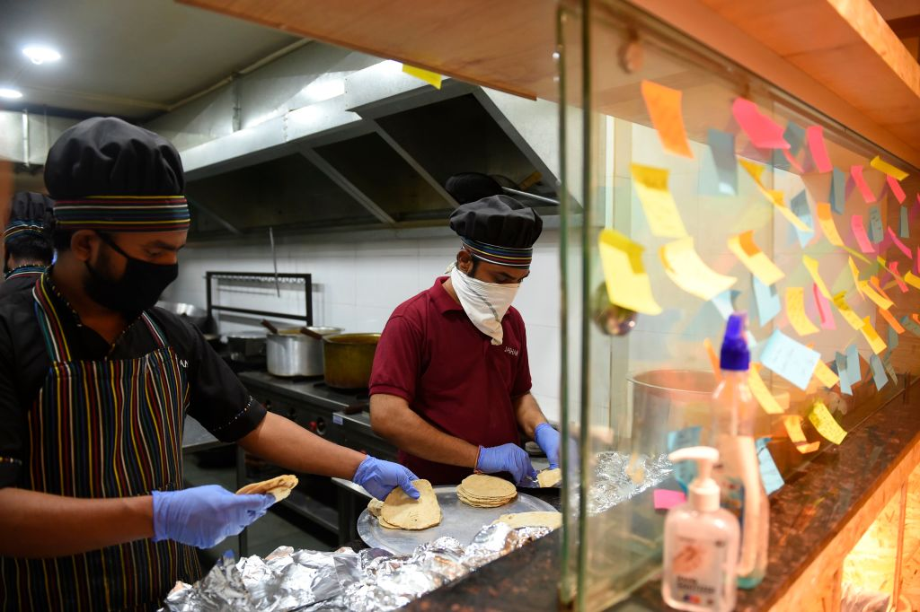 Workers prepare food packets in a shuttered restaurant to sell with a subsidised price to frontline workers fighting against the spread of the COVID-19 coronavirus in Ahmedabad on May 5, 2020. (Photo by SAM PANTHAKY/AFP via Getty Images)