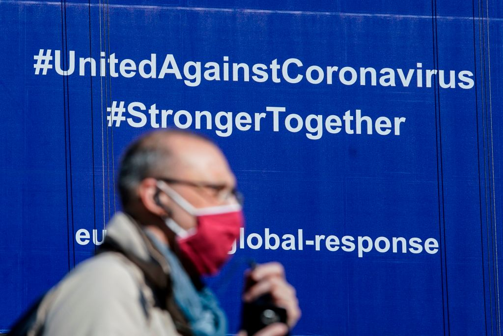 "A pedestrian wears a protective facemask as he walks past a newly hung banner that reads ""Coronavirus Global Response"" in front of The European Union (EU) Commission building in Brussels, on May 6, 2020. (Photo by KENZO TRIBOUILLARD/AFP via Getty Images)"