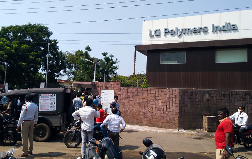 Policemen stand guard as people gather in front of an LG Polymers plant following a gas leak incident in Visakhapatnam on May 7, 2020. (Photo by -/AFP via Getty Images)